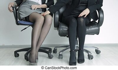 young woman in a suit is sexually harassing a beautiful girl in the office. Office lesbian harassment