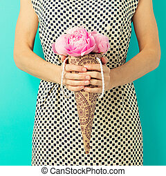 Young woman in a summer dress holding a bunch of peonies in hands on a turquoise wall background.