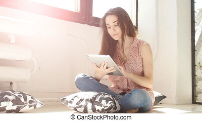 Young woman in a sunny room using a tablet