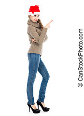 Young woman in a sweater and jeans pointing the finger side.