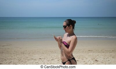 Young woman in a swimsuit with a phone on the beach