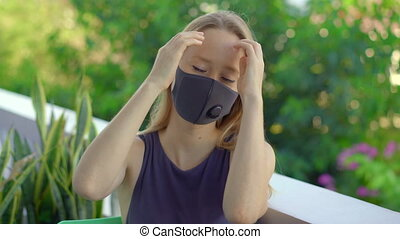 Young woman in a tissue face mask looks at the camera. Fashionable face masks. Social distancing concept