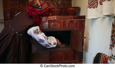 Young woman in a traditional ukrainian vyshyvanka costume puts raw bread dough in the oven. Handmade, housewife
