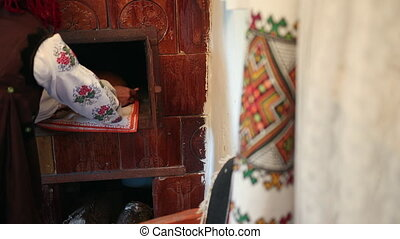 Young woman in a traditional ukrainian vyshyvanka costume puts raw bread dough in the oven. Handmade, housewife. Close up