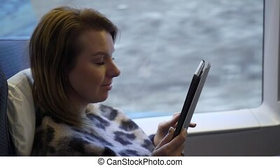 Young woman in a train car working with tablet