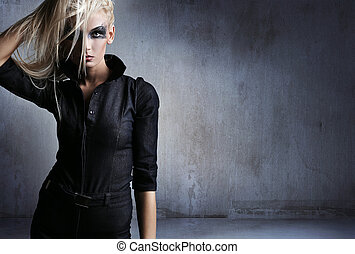 Young woman in a vampire look over grunge background