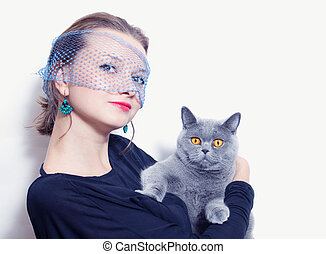 woman in a veil holding gray British cat