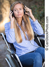 young woman in a wheelchair listening to music