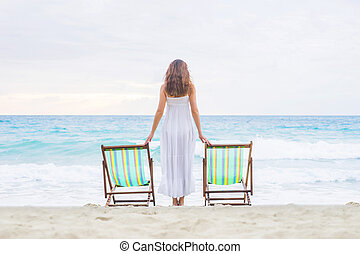 Young woman in a white dress posing on the beach