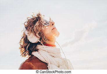 Young woman in a white headphones listening to music bright sky background in summer day