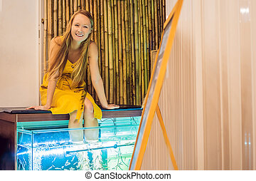 Young woman in a yellow dress at the fish spa