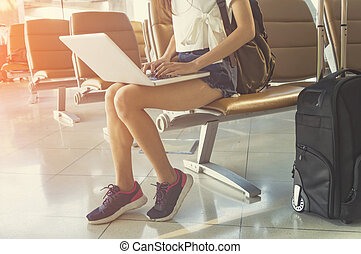 Young woman in airport waiting for air travel using tablet. She is sitting with travel suitcase trolley, in waiting hall of departure lounge in airport.