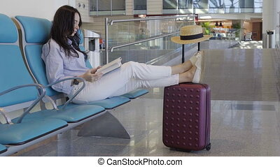 Young woman in an airport lounge reading book while waiting for flight aircraft.
