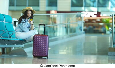 Young woman in an airport lounge waiting for flight aircraft. Caucasian woman with smartphone in the waiting room