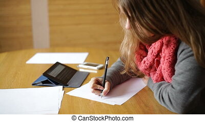young woman in an office hands writing on paper