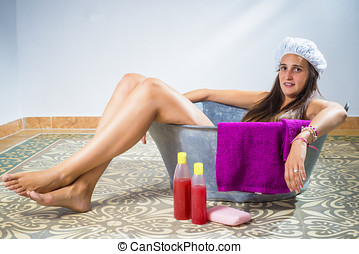 Young woman in an old bathtub