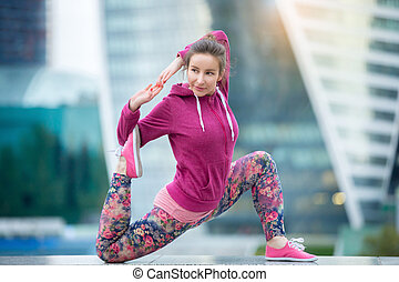 Young woman in anjaneyasana pose against the city