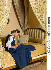 Young woman in antique canopy bedroom