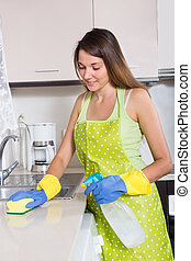 young  woman in apron cleaning kitchen sink in interior