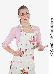 Young woman in apron holding spatula
