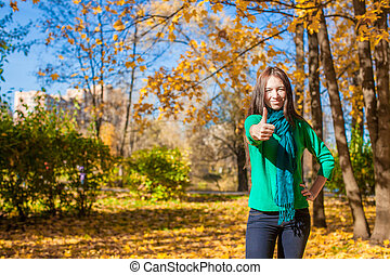 Young woman in autumn yellow park showing a thumbs up