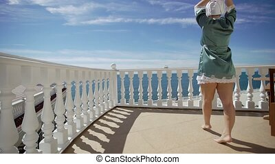 Young woman in bathrobe comes to balcony