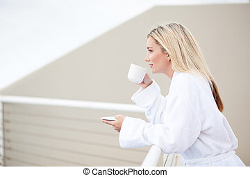 young woman in bathrobe drinking coffee on balcony in the ...