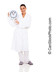 young woman in bathrobe holding clock