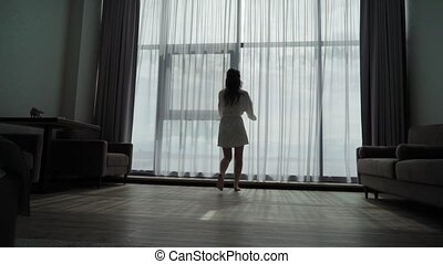 Young woman in bathrobe in bedroom opening curtains at panoramic window