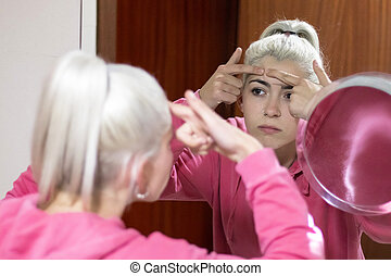 woman in bathrobe looking at pimple on face into the mirror and try to squeeze it.