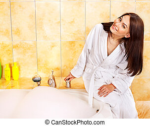 Young woman in bathroom. - Young woman filling bathtube with...