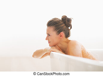 Young woman in bathtub looking on copy space