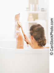 Young woman in bathtub using body brush on leg