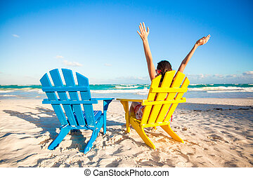 Young woman in beach chair raised her hands up on white...