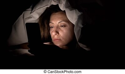 Young woman in bed with smartphone. Woman starring at cellphone device before going to bed in 4k