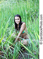 young woman in bikini amid green grass