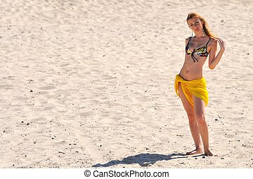 Young woman in bikini and pareo standing on sandy beach