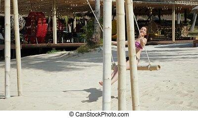 Young woman in bikini on a swing
