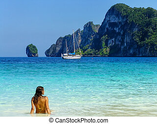 Young woman in bikini sitting at Ao Yongkasem beach on Phi Phi Don Island, Krabi Province, Thailand