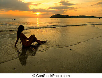 Young woman in bikini sitting on a beach at sunset, Langkawi island, Malaysia, Southeast Asia