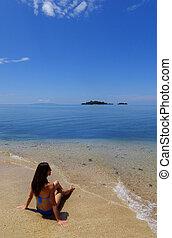 Young woman in bikini sitting on a beach, Vanua Levu island, Fiji, South Pacific