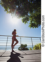 Young woman in bikini standing by railing with cocktail