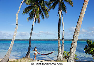 Young woman in bikini standing by the hammock between palm trees
