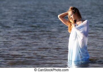 Young woman in bikini standing in water in sunshine