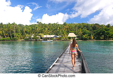 Young woman in bikini standing on a long wooden pier, Nananu-i-R