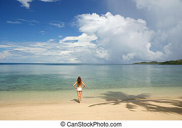 Young woman in bikini standing on a tropical beach, Nananu-i-Ra