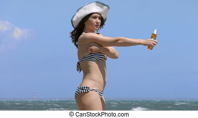 """Young woman in bikini suntanning on beach at seaside, applying suncream on body"""