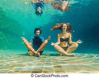 young woman in black bikini and man in yoga position underwater in diving aquarium, full body shot, front view