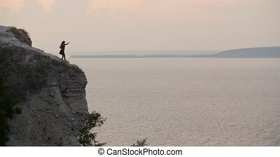 Young woman in black dress dancing on the edge of the cliff by the sea