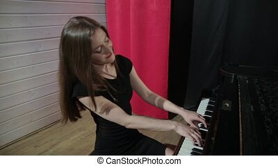 Young woman in black dress playing on the piano